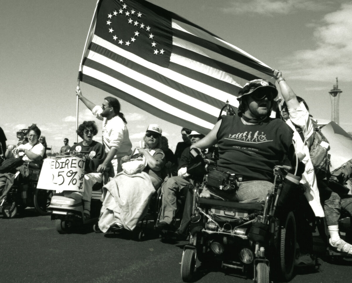Image by Tom Olin that shows Vegas Advocacy walk and ride for disability rights with disability flag
