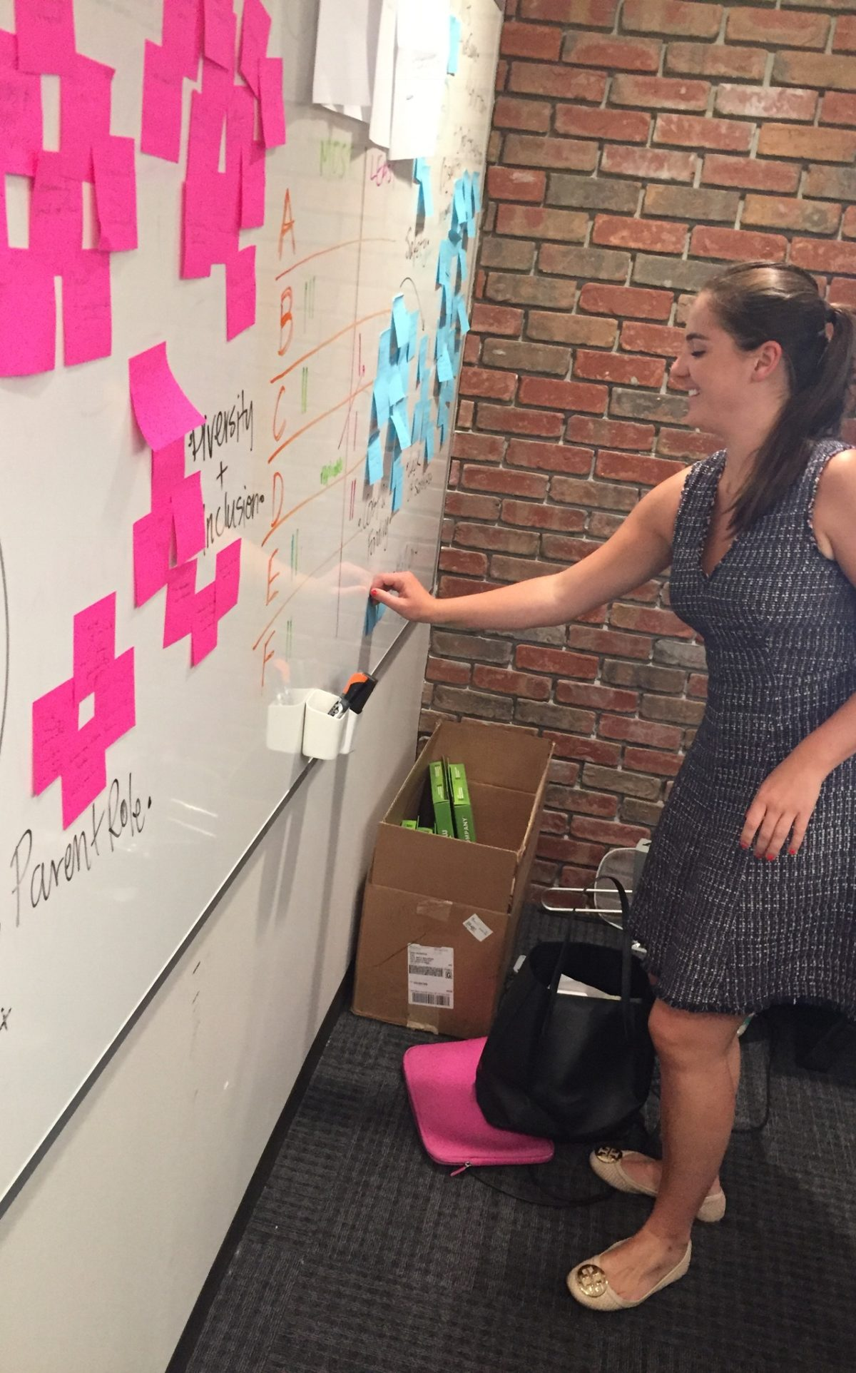 Photo of Lindsay, woman with dark hair pulled back in grey dress, posting pink posted notes on wall.