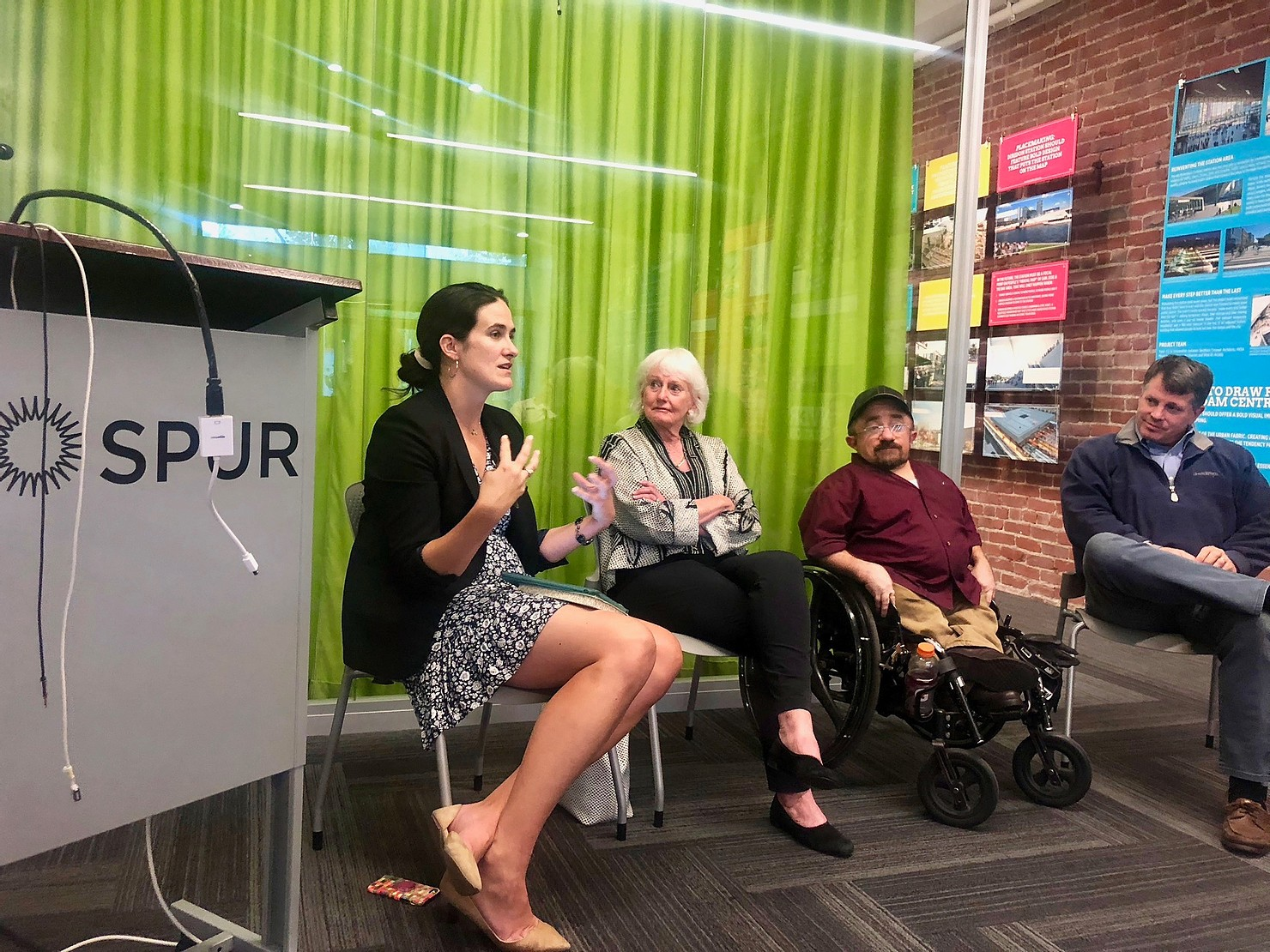 Micaela speaking with panelists for SPUR
