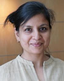 image of Vinita, a person of color with hair up smiling at camera wearing a tan shirt.
