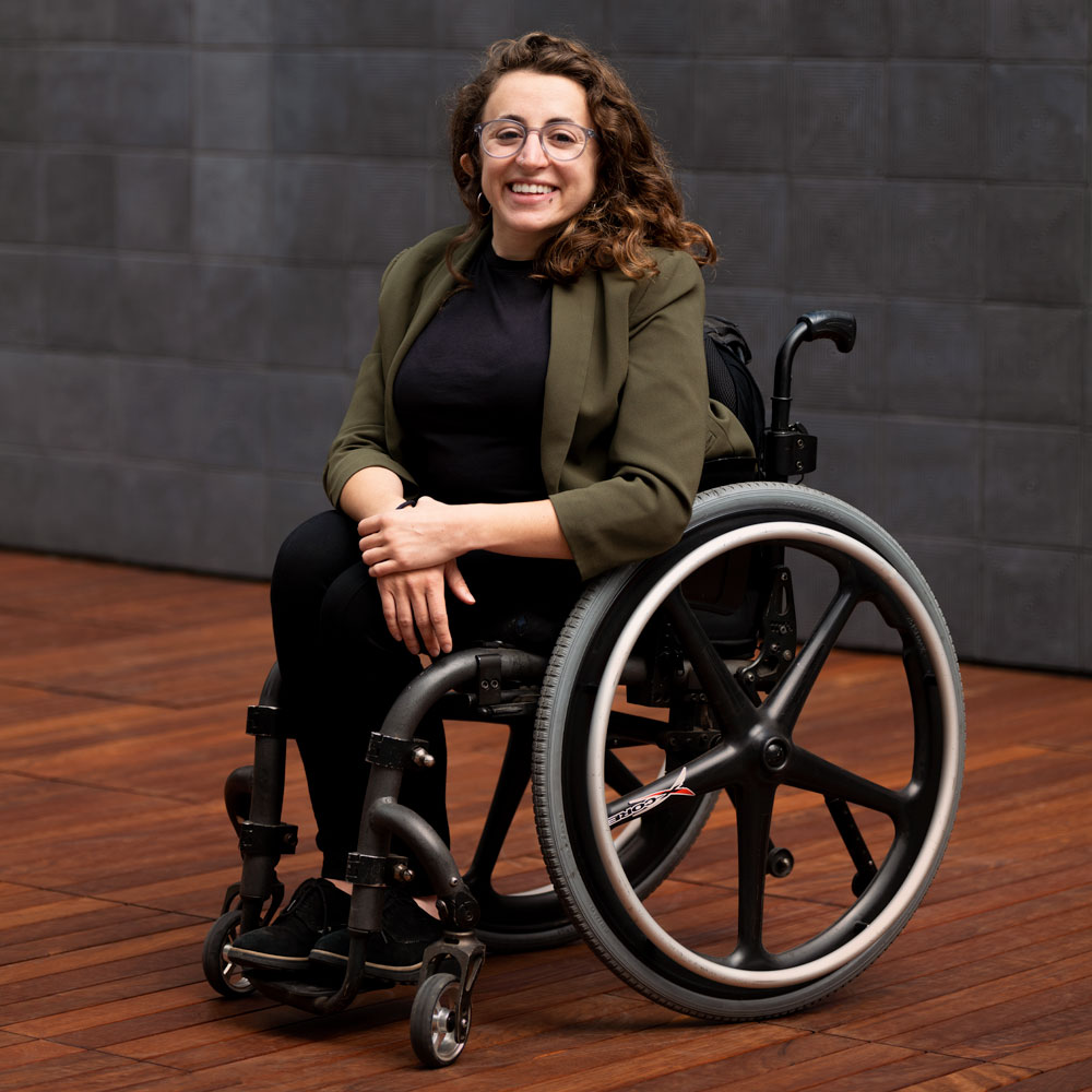 white queer person in a wheelchair smiling with glasses short brown hair, green blazer and black pants and shirts
