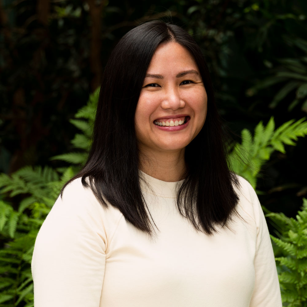 Photo image of Ann, an Asian American woman with shoulder length straight black hair wearing a light cream colored sweater and smiling.