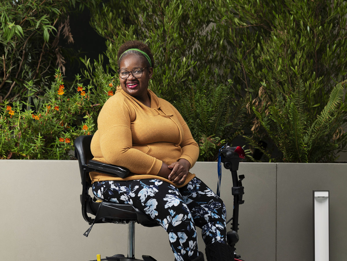 Black women wearing orange sweater, patterned pants, eye glasses, headband, staring and smiling at camera in her power chair. Greenery behind her.
