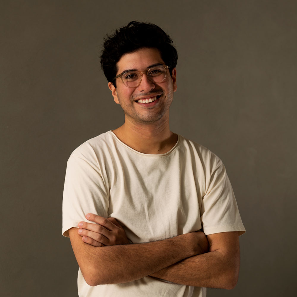 Eric is a white Hispanic man with dark brown hair and clear framed glasses. He's shown crossing his arms and smiling at the camera in a tan-colored shirt.