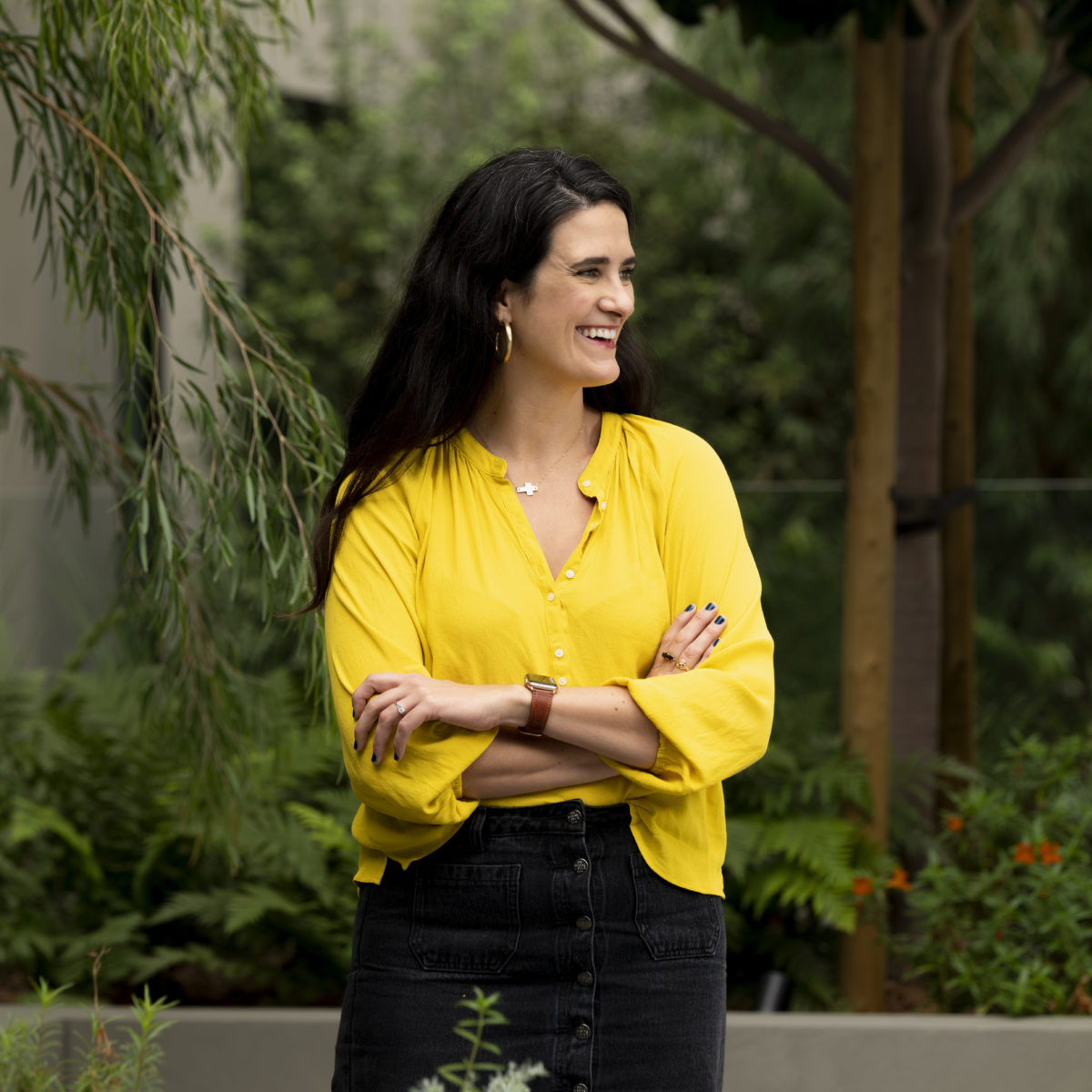 Micaela is white woman in her thirties. She has long brown hair, and is wearing a yellow blouse and black skirt. There is greenery surrounding her.