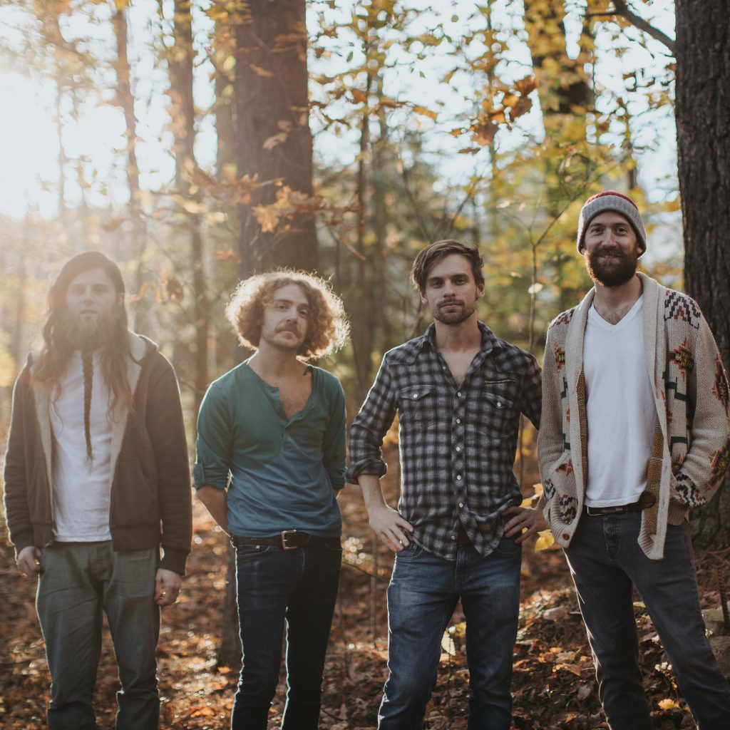 Four male band members make up Paronsfield, shown here. They are each lined up in a wooded area with Fall leaves behind them. They are all staring at the camera as the sun shines behind them.