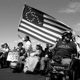 Black and white image of people with disabilities rally with American Flag in the air with wheelchair over it.