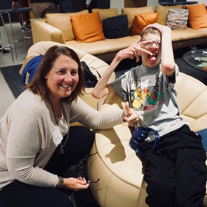 Image of woman and her adult son sitting on a chair. Son is making silly face and hand gesture at camera.