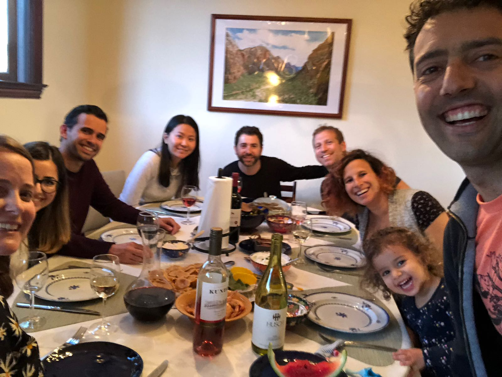 Photo of Caroline and her family all sitting around a dining table smiling at camera.