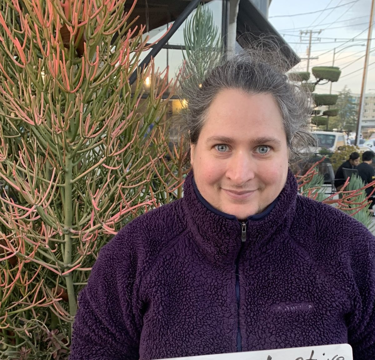Myra, a young white woman with green eyes, wearing a purple jacket, smiling at the camera with a plant behind her.