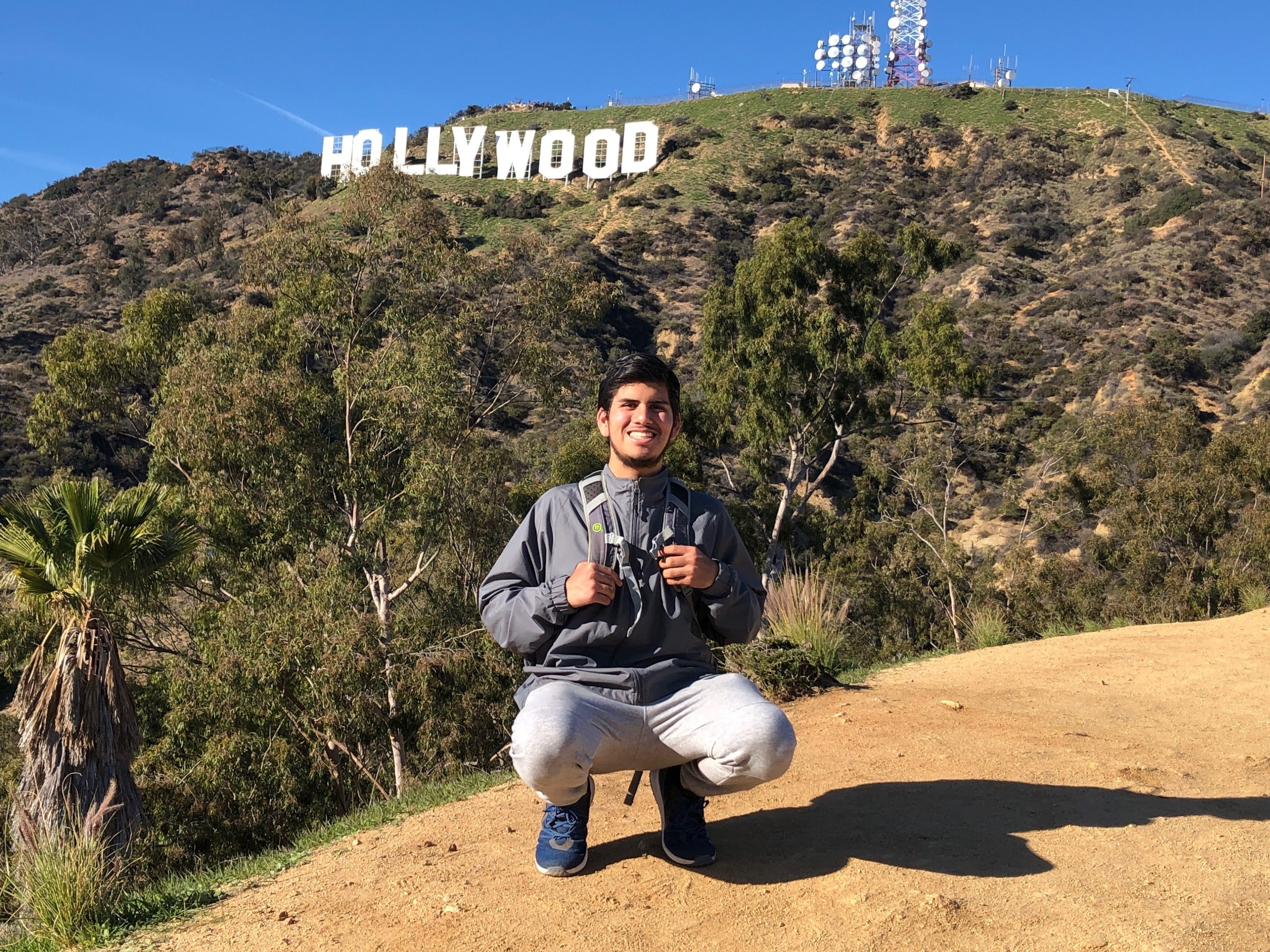 Raul, hispanic male in athletic clothing with a backpack on a hike in Los Angeles with the Hollywood sign behind him.