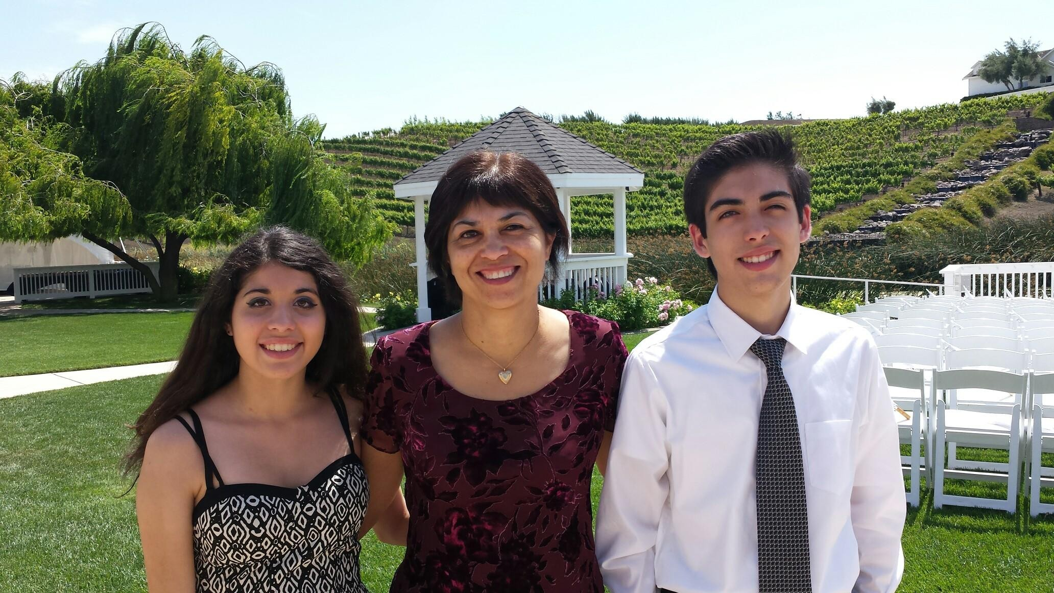 Kristina, middle aged woman in center with two young adult children beside her. They are each smiling at camera with scenic view behind them. They each have brown hair, and dressed formal attire.
