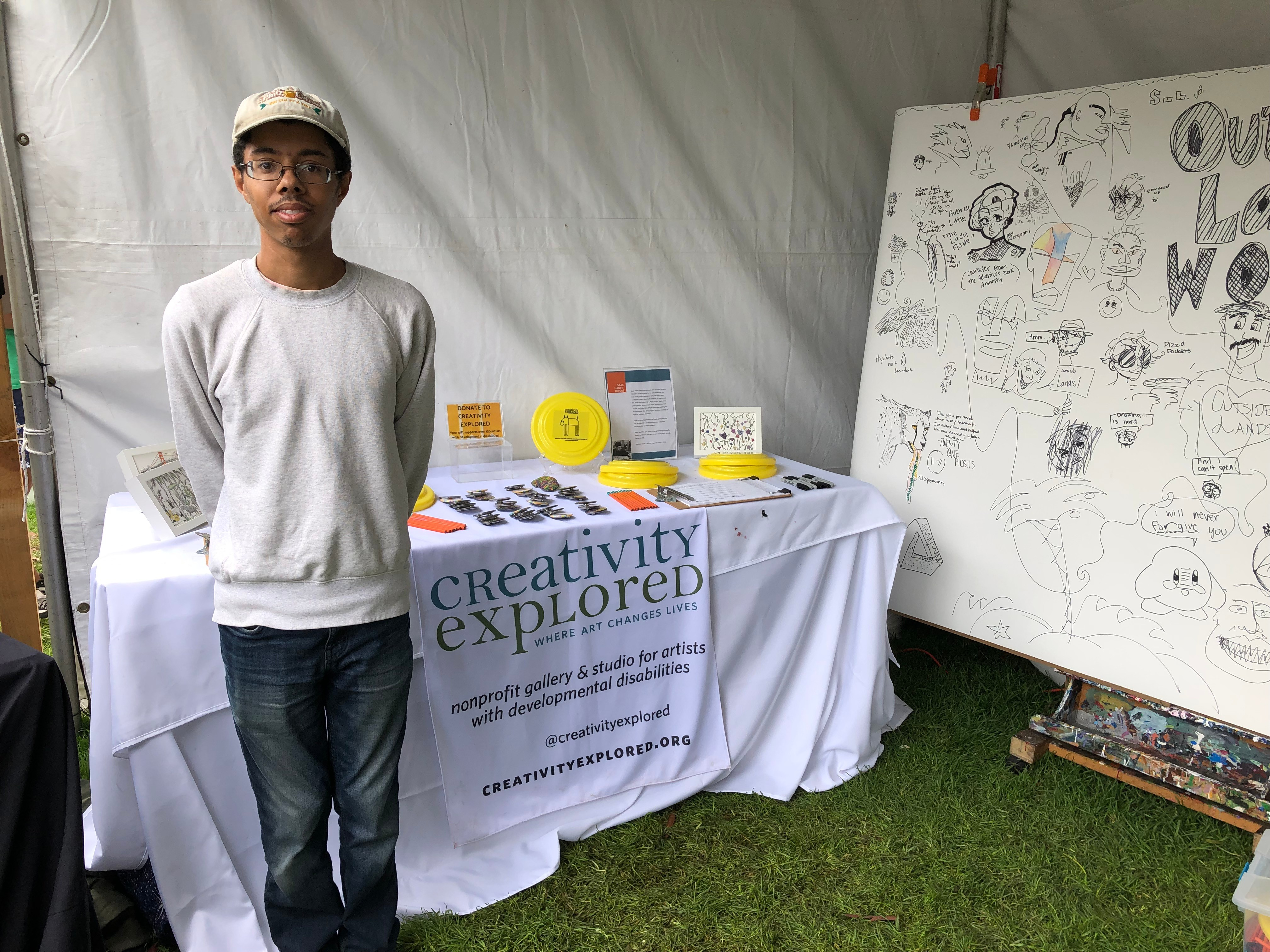 Isaac, black male smiling at camera, wearing glasses and a hat, standing in front of Creativity Explored table at event.
