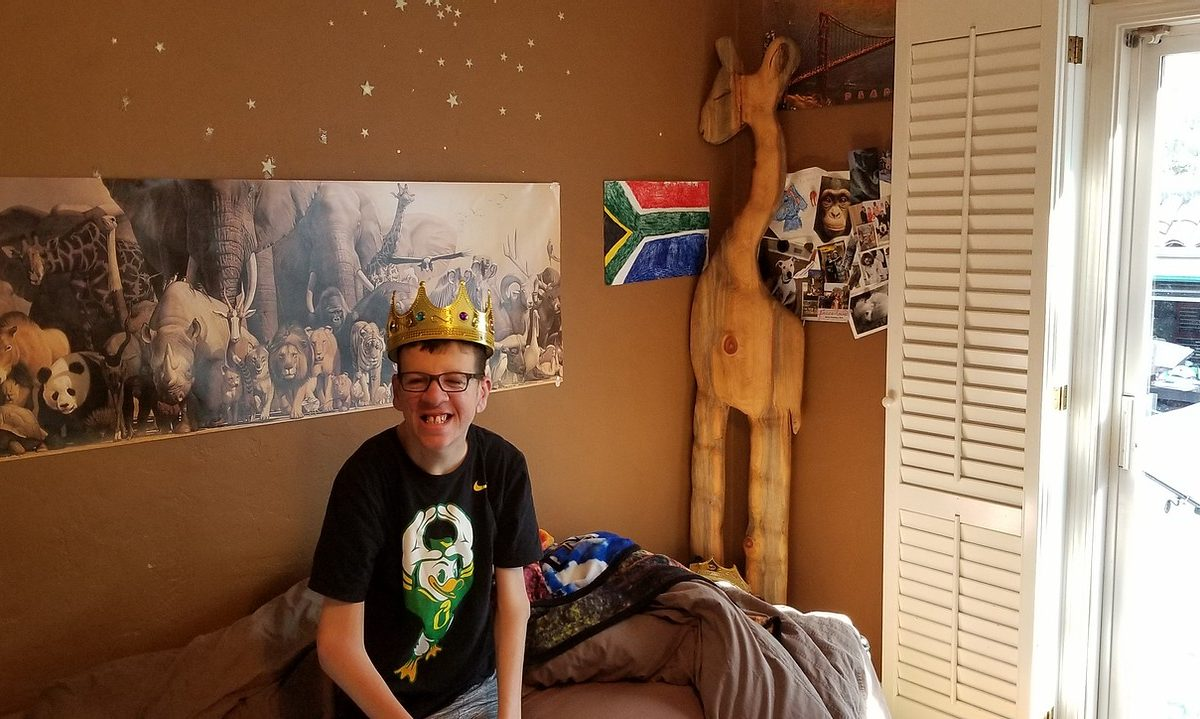 Robbie, white young adult male sitting in his bedroom, with a wooden giraffe behind him. He is smiling, wearing glasses, and a crown on his head.
