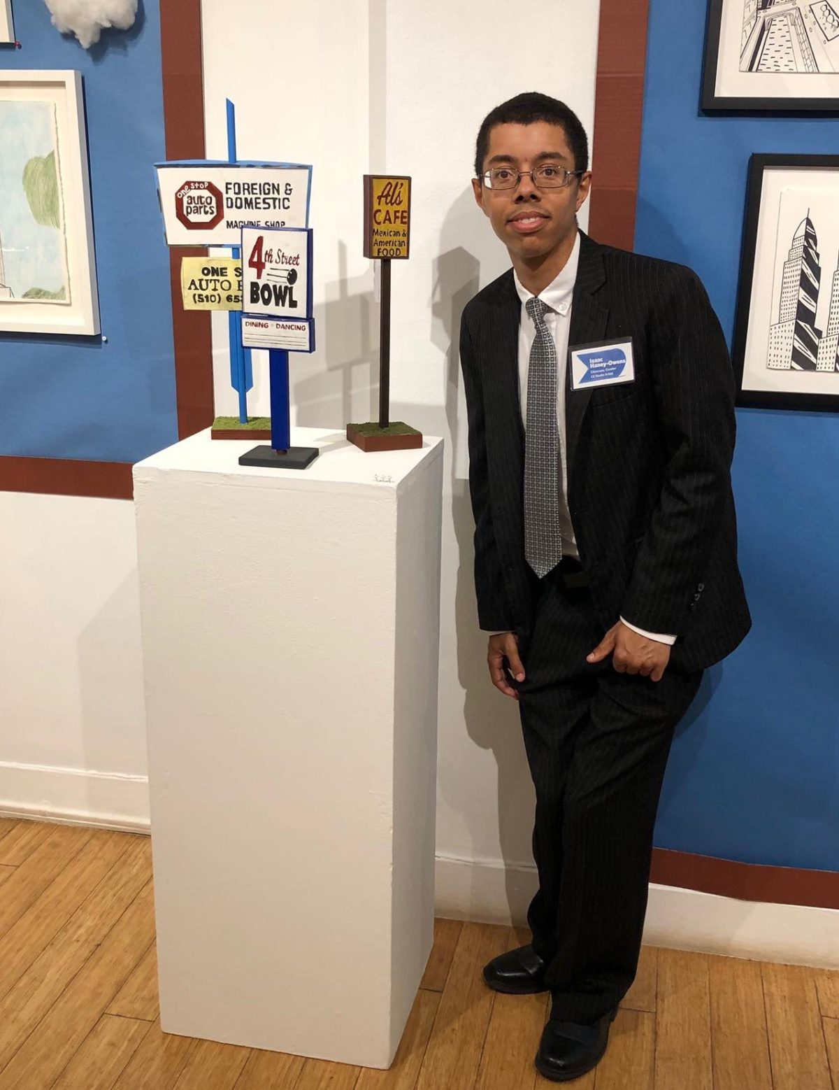 Isaac, a black young man, wearing a suit and eye glasses next to his art featured at Creativity Explored
