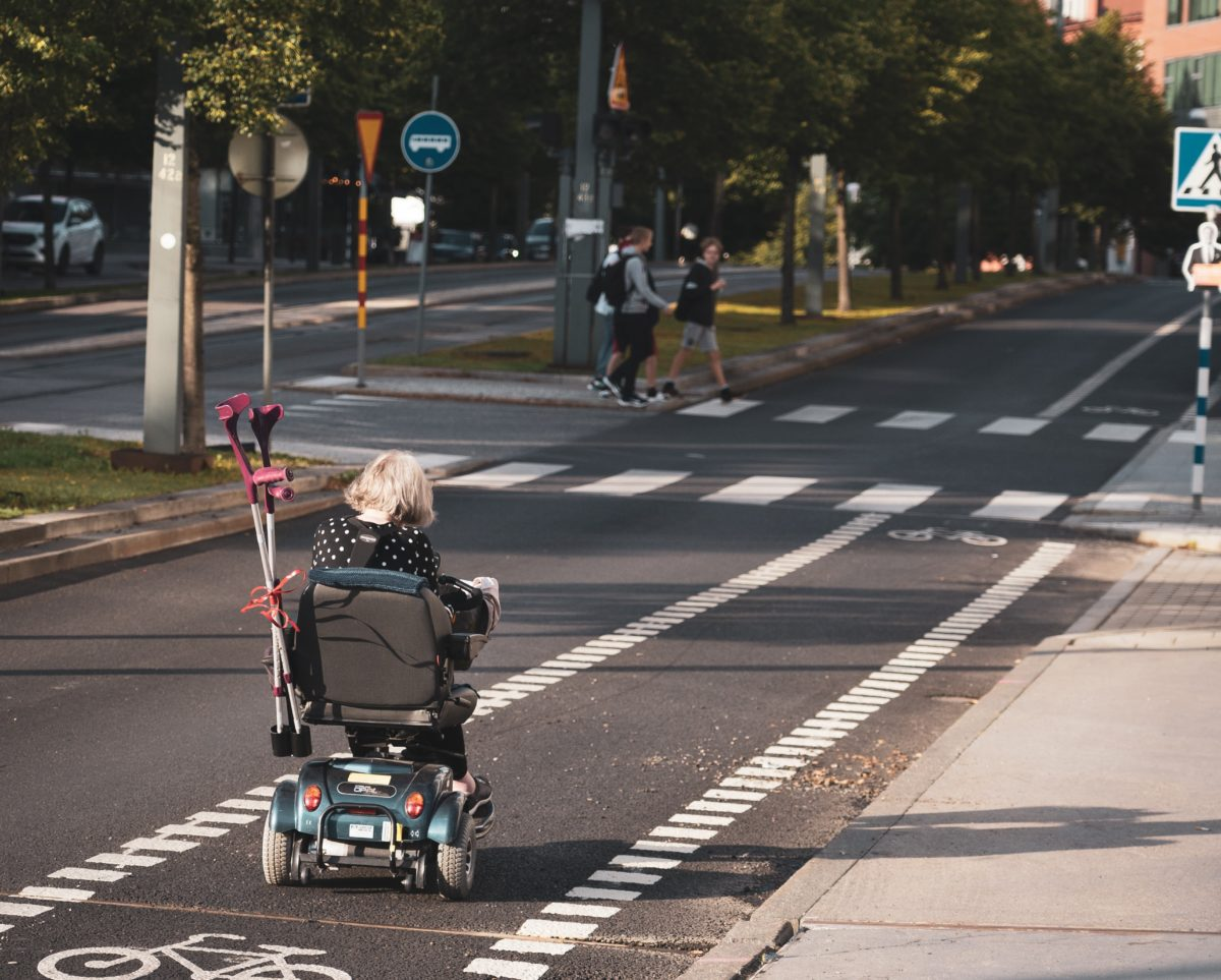 lady in power chair storing crutches in the back of her chair as she drives down the street using bike lane.