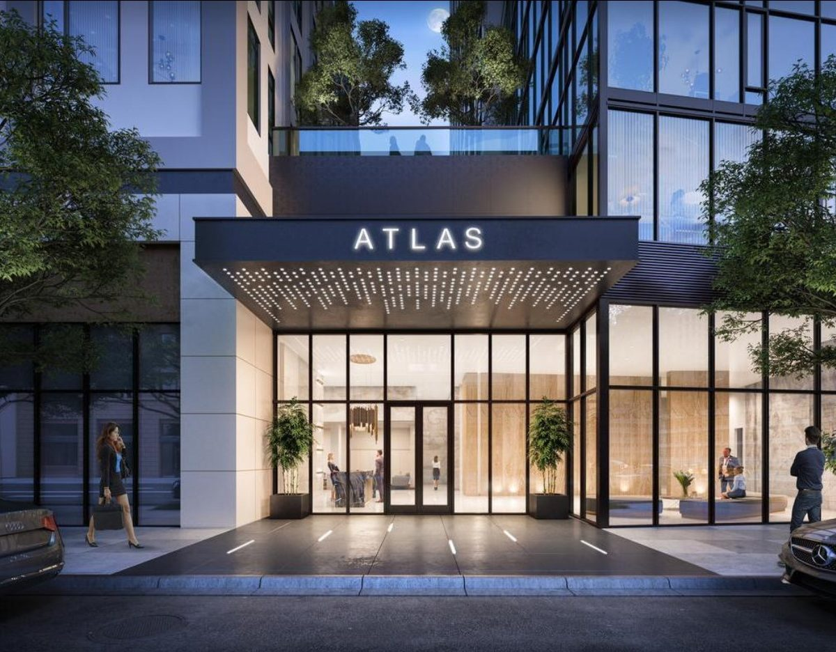 Entrance to Atlas. Sign says atlas on roof. Large glass door greet you with greenery shown in courtyard peaking through.