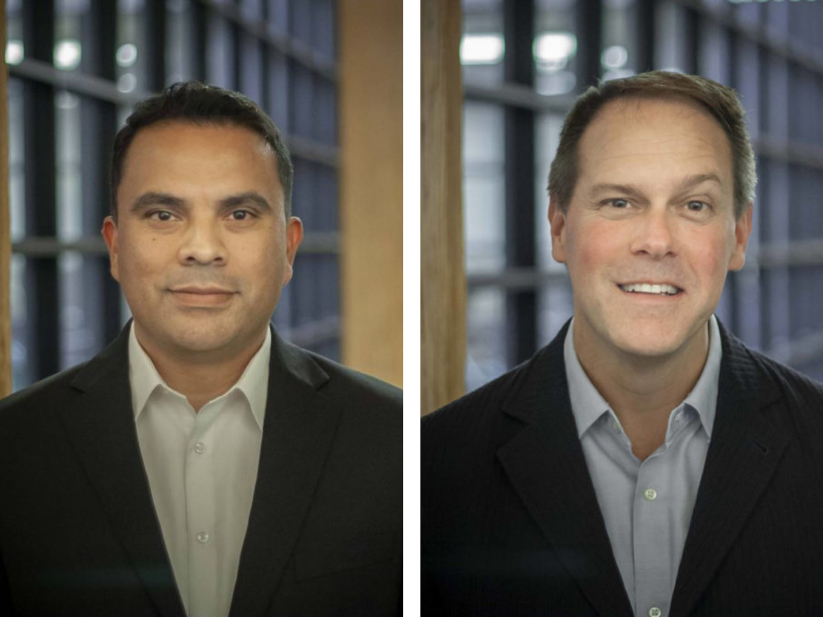 Image of Armando on left and Steve on right. Armando is a hispanic male with short dark hair, smiling at camera wearing collard shirt and blazer in office setting. Steve is a white man with short brown hair and wearing a collard shirt and blazer in the same office setting.