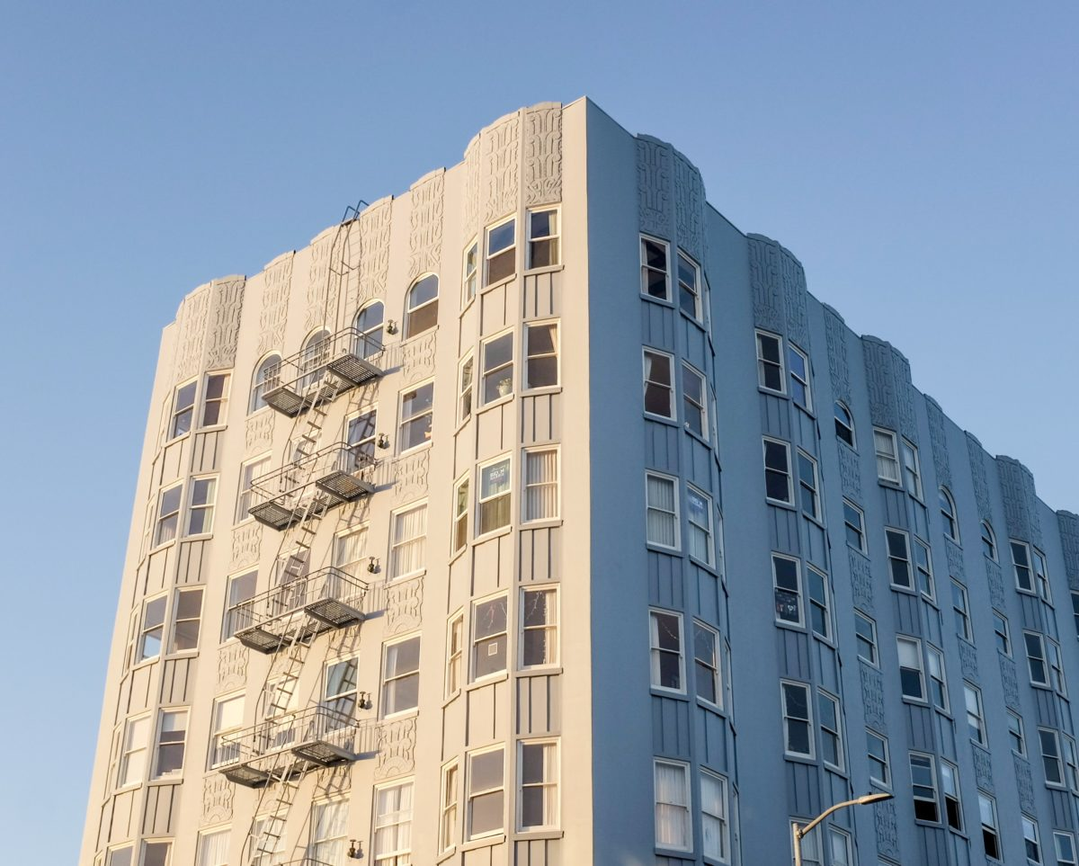 image of multifamily housing building in California. The photo looks up at the top of the building with the blue sky surrounding it. The building is white and there are 5 stories shown.