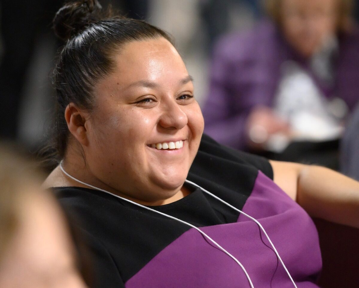 Dolores, hispanic woman smiling at someone to the camera's right with hair pulled up, wearing a black and purple shirt