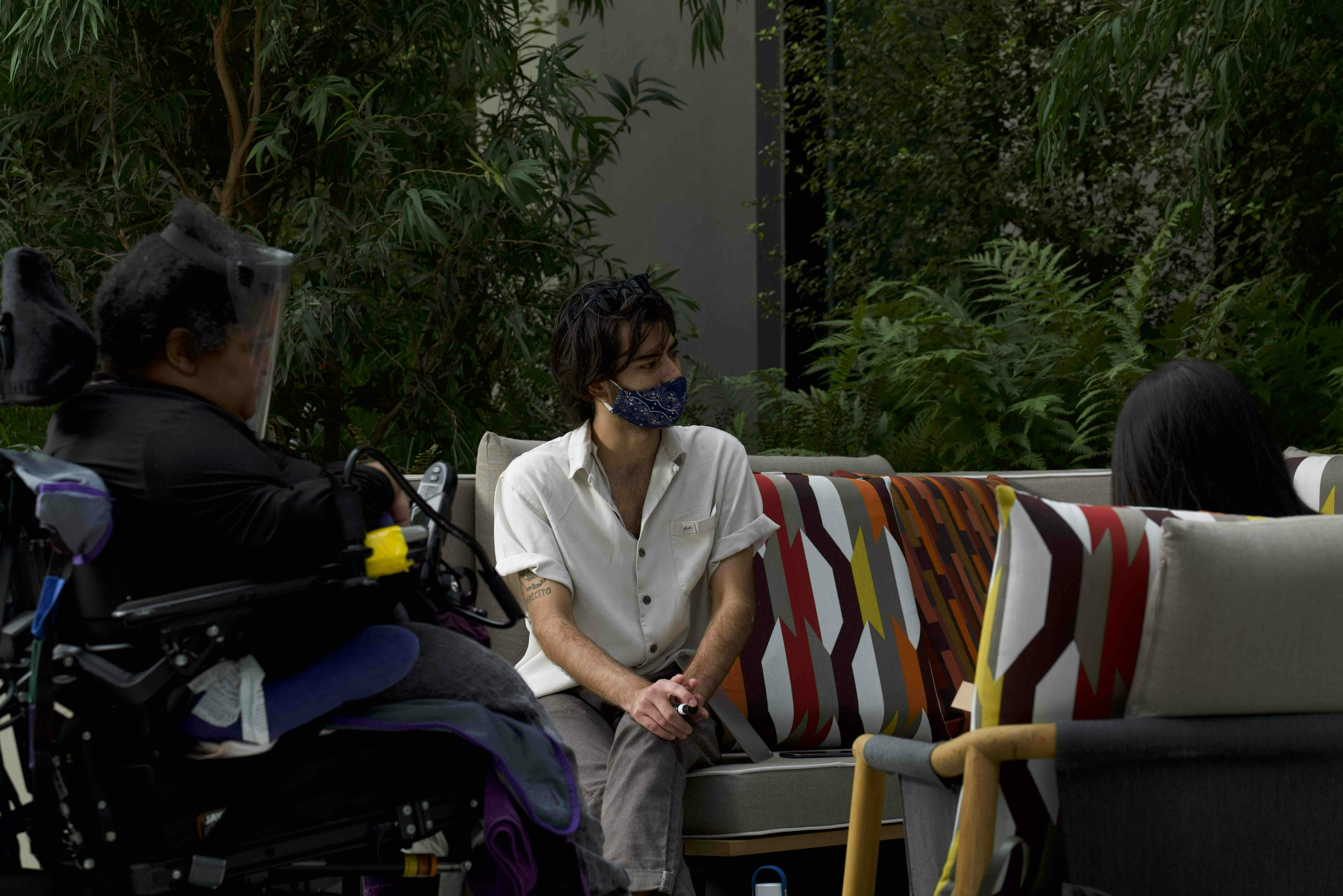 Image of support staff and person with disabilities sitting in wheelchair. There is greenery surrounding them.