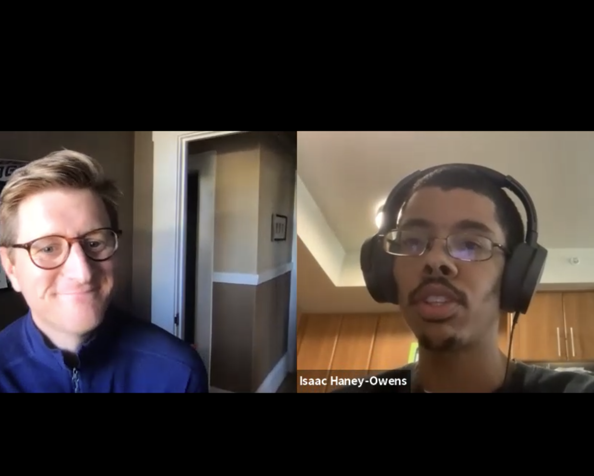 screenshot of Isaac & Graeme's interview together. Graeme is a white man with short hair wearing a navy shirt and glasses smiling at screen. Isaac is a mixed race black man with short hair and facial hair. He is shown with glasses and headphones speaking at screen.