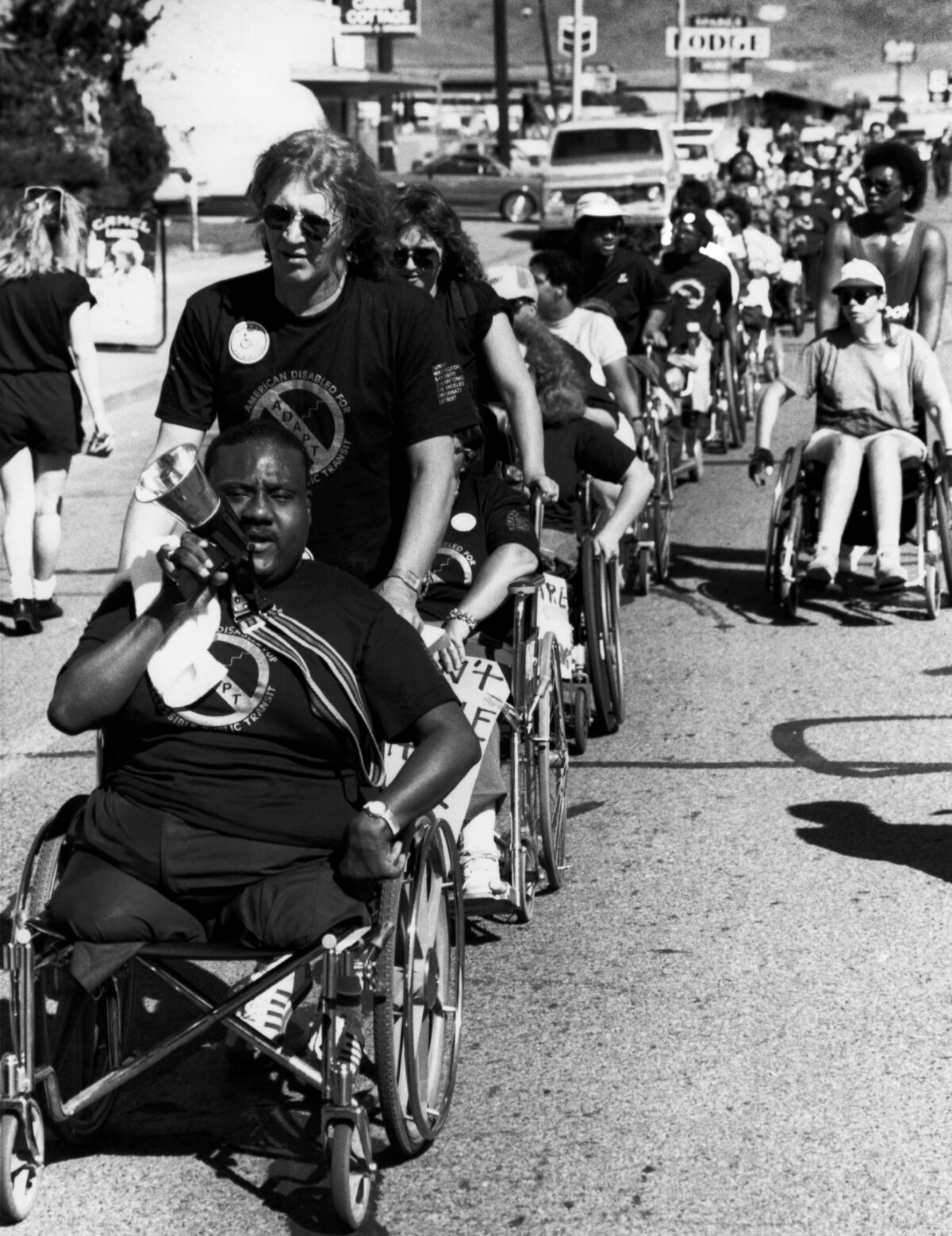 image of disability rights march with black disabled man in wheelchair at from with white man pushing him. There looks to be over 100 people present