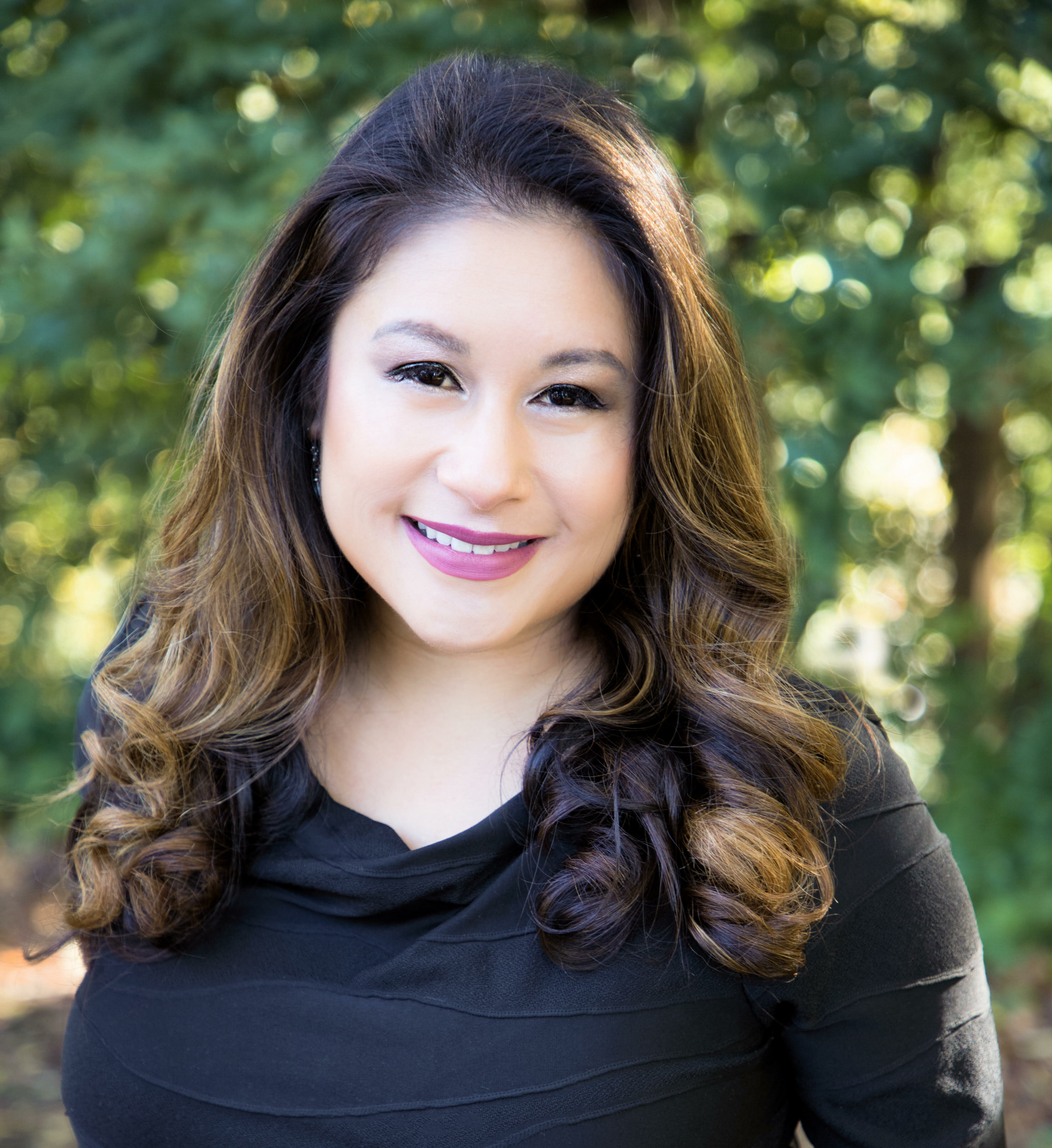 Filipino-American woman smiling at camera, wearing lipstick with long curly brown hair, brown eyes and black blouse. She is outdoors and there is greenery behind her